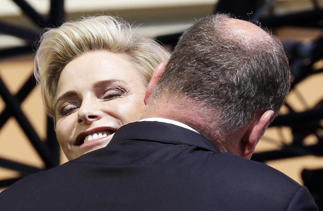 Princess Charlene of Monaco and Prince Albert II of Monaco embrace during celebrations marking the 10th anniversary of Prince Albert II of Monaco's accession to the throne, on July 11, 2015, in Monaco. On 31 March 2005, the Palace of Monaco announced that Hereditary Prince Albert would take over the duties of his father as regent since Rainier was no longer able to exercise his functions as sovereign. On 6 April 2005, Prince Rainier III died and Hereditary Prince Albert became Albert II, Sovereign Prince of Monaco. AFP PHOTO / POOL / LIONEL CIRONNEAU