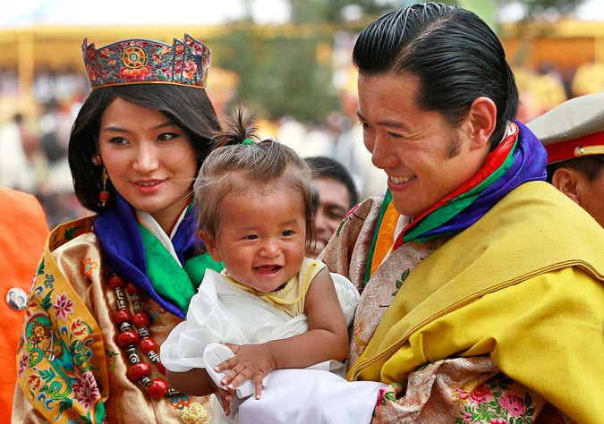 King Jigme Khesar Namgyal Wangchuck, right, holds a young child as he greets locals with Queen Jetsun Pema during a celebration after they were married at the Punakha Dzong in Punakha, Bhutan, Thursday, Oct. 13, 2011. The 31-year-old reformist monarch of the small Himalayan Kingdom wed his commoner bride in a series ceremonies Thursday in the 17th century monastic fortress. (AP Photo/Kevin Frayer)