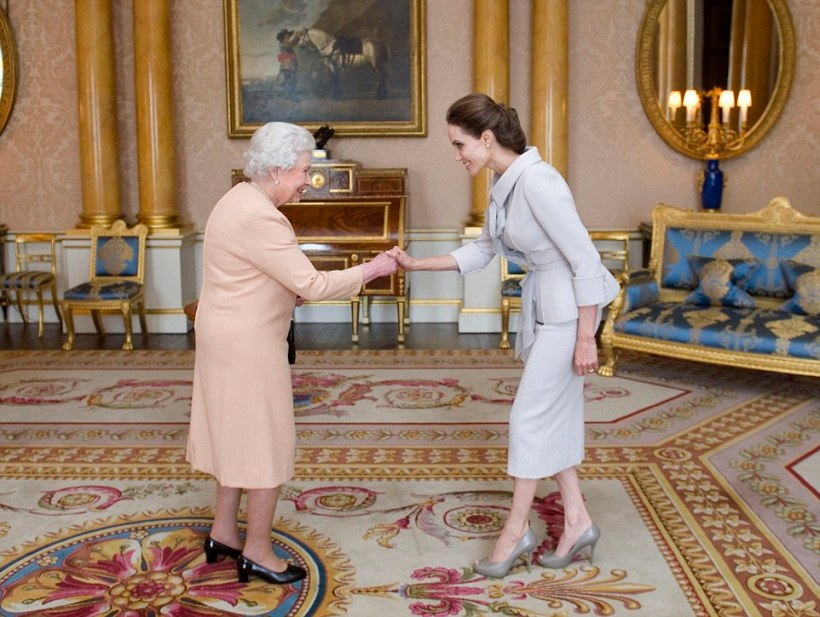 Actress Angelina Jolie is presented with the Insignia of an Honorary Dame Grand Cross of the Most Distinguished Order of St Michael and St George by Queen Elizabeth II in the 1844 Room at Buckingham Palace, London. PRESS ASSOCIATION Photo. Picture date: Friday October 10, 2014. Jolie is receiving an honorary damehood (DCMG) for services to UK foreign policy and the campaign to end war zone sexual violence. Photo credit should read: Anthony Devlin/PA Wire